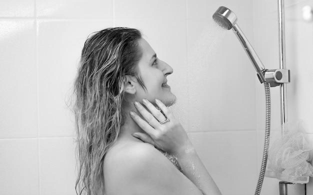 Czarno-biały portret pięknej kobiety myjącej włosy pod prysznicem