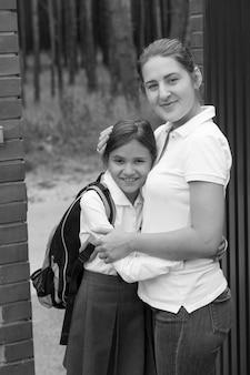 Czarno-biały portret pięknej przytulonej matki i córki w szkolnym mundurku