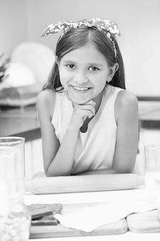 Czarno-biały portret ślicznej uśmiechniętej dziewczyny pozuje na kuchni podczas robienia ciasta