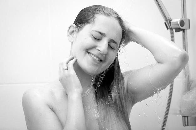 Czarno-biały portret uśmiechniętej kobiety myjącej włosy pod prysznicem