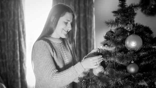 Czarno-biały portret uśmiechniętej młodej kobiety dekorującej choinkę o poranku