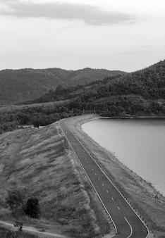 Czarno-biały tamy i drogi przed tamą w górach.