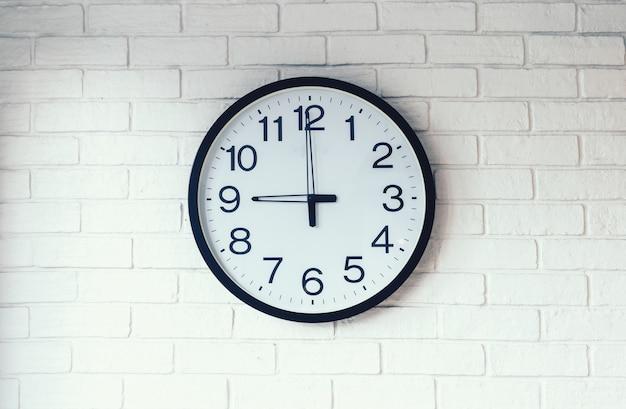Czarno-biały zegar na tle białej cegły ściany. na zegarze, dziewięć na zegarze.