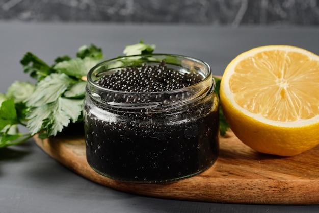 Czarno-czerwony kawior w szklanych słoikach z pietruszką i cytryną.