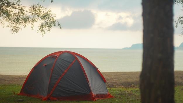 Czarno-czerwony namiot na brzegu w pobliżu pięknego morza pod pochmurnym niebem