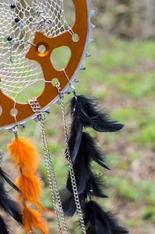 Czarno-pomarańczowy łapacz snów z gwiazdą z piór, skórzanych koralików i sznurków, wiszący
