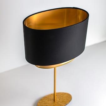 Czarno-złota lampa z przodu zaprojektowana z wyjątkową dekoracją na białym tle
