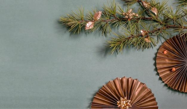 Czarno-złoty papierowy fan i gałąź drzewa cristmas na zielonym tle