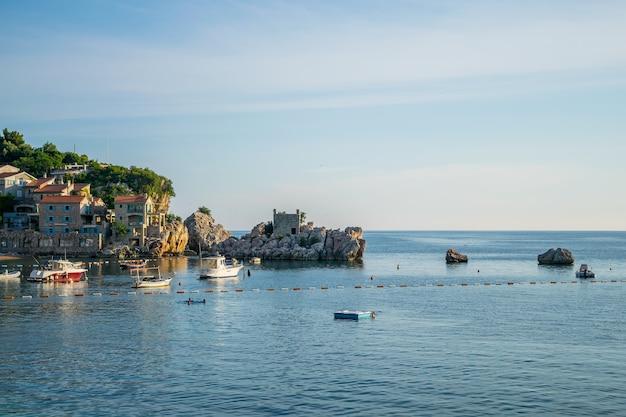 Czarnogóra, przno. turyści pływają w morzu adriatyckim podczas zachodu słońca.