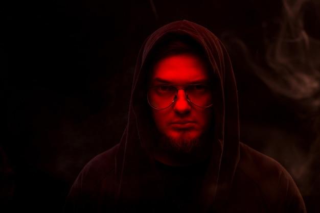 Czarnoksiężnik z czerwoną twarzą w kapturze i okularami na czarnym tle w dymie.