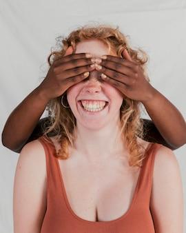 Czarnoskóra ręka kobiety zakrywająca oczy swojego pięknego przyjaciela na szarym tle