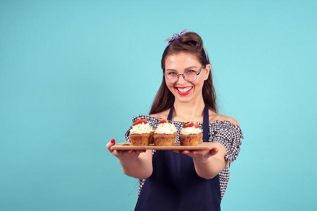 Czarnowłosa ciasto szefa kuchni kobieta pozuje dla kamery z centami w jej rękach na błękitnym tle