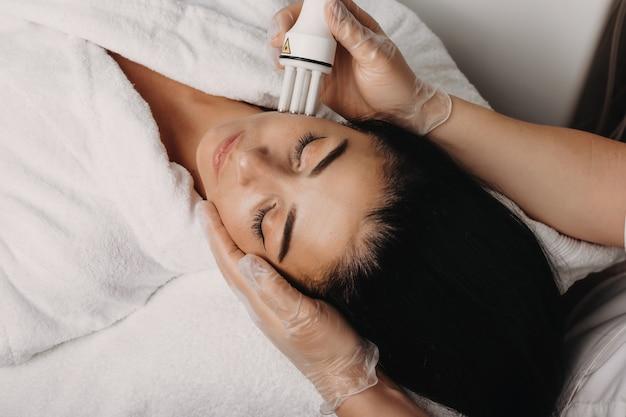 Czarnowłosa kaukaska kobieta o zabiegu spa przeciw starzeniu na twarzy