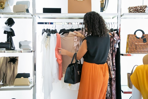 Czarnowłosa kobieta wybiera ubrania i przegląda sukienki i koszule na stojaku. widok z tyłu. koncepcja sklepu mody lub sprzedaży detalicznej