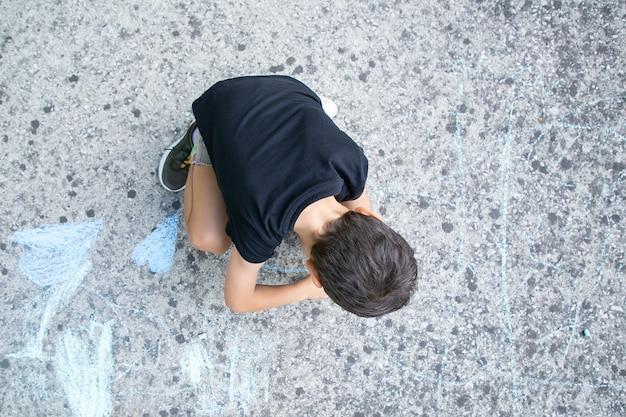 Czarnowłosy mały chłopiec siedzi i rysuje na asfalcie z kolorowymi kawałkami kredy. widok z góry. koncepcja dzieciństwa i kreatywności