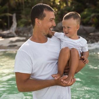 Czarnowłosy młody, brodaty ojciec trzyma w ramionach swoje małe dziecko z synkiem o blond włosach.