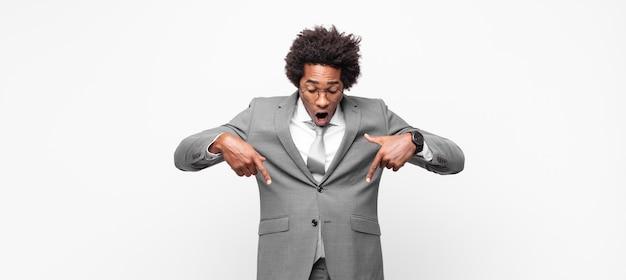 Czarny afro biznesmen czuje się zszokowany, z otwartymi ustami i zdumiony, patrząc i wskazując w dół z niedowierzaniem i zaskoczeniem