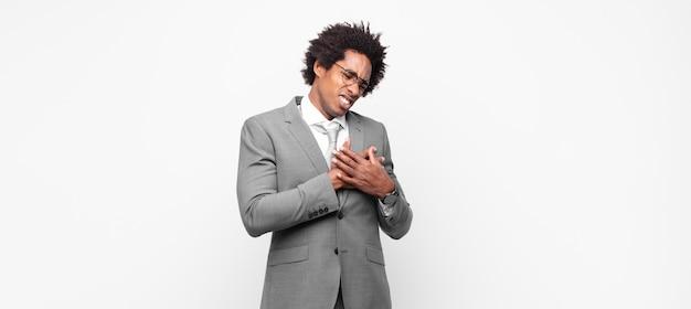 Czarny afro biznesmen wyglądający na smutnego, zranionego i załamanego, trzymający obie ręce blisko serca, płaczący i przygnębiony