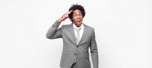 Czarny afro biznesmen, wyglądający na szczęśliwego, zdziwionego i zdziwionego, uśmiechnięty i uświadamiający sobie niesamowite i niewiarygodnie dobre wieści