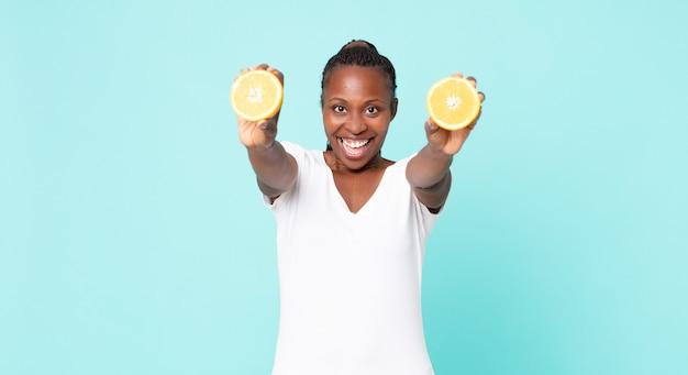Czarny afroamerykanin dorosła kobieta. koncepcja soku pomarańczowego