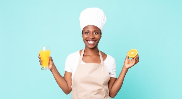 Czarny afroamerykanin dorosła kobieta kucharz. koncepcja soku pomarańczowego