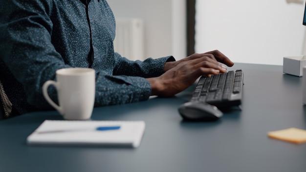 Czarny afroamerykański menedżer pracujący w domu, tuping na klawiaturze komputera