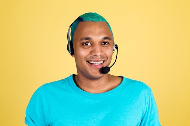 Czarny afrykański mężczyzna dorywczo na żółtej ścianie niebieskie włosy pracownik call center szczęśliwy operator obsługi klienta ze słuchawkami