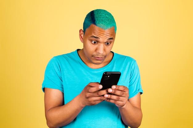 Czarny afrykański mężczyzna dorywczo na żółtej ścianie z telefonem komórkowym na ekranie zszokowany unosi brwi
