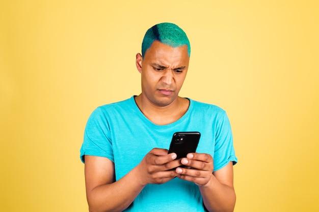Czarny afrykański mężczyzna na co dzień na żółtej ścianie z telefonem komórkowym wygląda z obrzydzeniem, niezadowoloną twarzą negatywnych emocji
