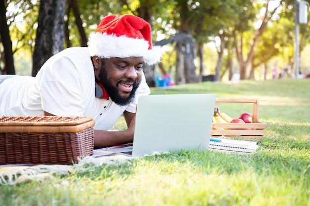 Czarny afrykański mężczyzna w czapce świętego mikołaja i za pomocą laptopa do komunikacji w ogrodzie