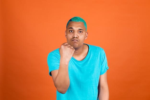 Czarny afrykański mężczyzna w dorywczo na pomarańczowej ścianie niebieskie włosy krzycząc zły podnosząc pięść nieszczęśliwy i agresywny