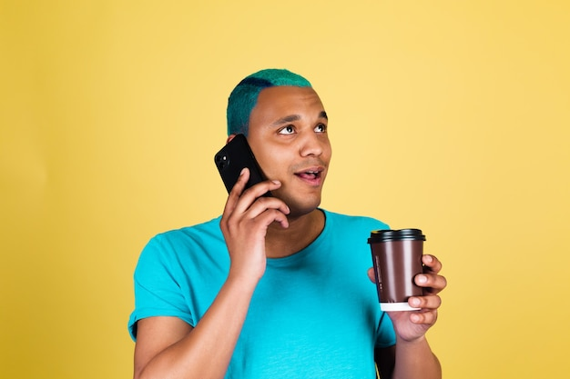 Czarny afrykański mężczyzna w dorywczo na żółtej ścianie niebieskie włosy, ciesząc się filiżanką kawy, pozytywne szczęśliwe emocje rozmawia przez telefon, uśmiech i śmiech