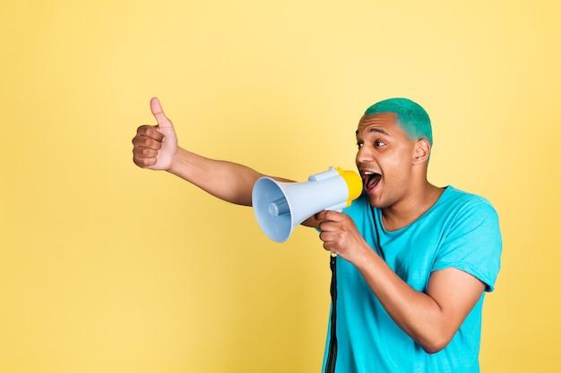 Czarny afrykański mężczyzna w dorywczo na żółtej ścianie niebieskie włosy krzycząc w megafon w lewo pokazuje kciuk w górę