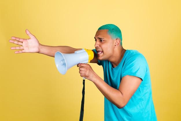 Czarny afrykański mężczyzna w dorywczo na żółtej ścianie niebieskie włosy krzycząc w megafon w lewo