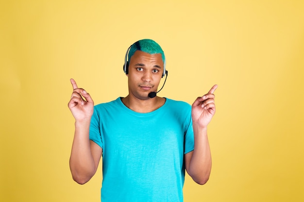 Czarny afrykański mężczyzna w dorywczo na żółtej ścianie pracownik centrum telefonicznego niebieskie włosy szczęśliwy operator obsługi klienta ze słuchawkami wskazuje palcami w górę