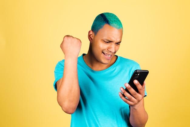 Czarny afrykański mężczyzna w dorywczo na żółtej ścianie z pięścią zaciskającą telefon komórkowy obchodzi gest zwycięzcy
