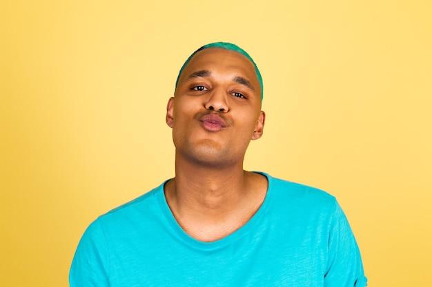 Czarny afrykański mężczyzna w swobodnym stylu na żółtej ścianie pozytywnie patrzy na aparat i wysyła pocałunek