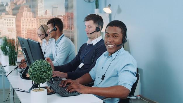 Czarny agent obsługi klienta pracuje w zajętym centrum telefonicznym, rozmawiając z klientem międzynarodowym