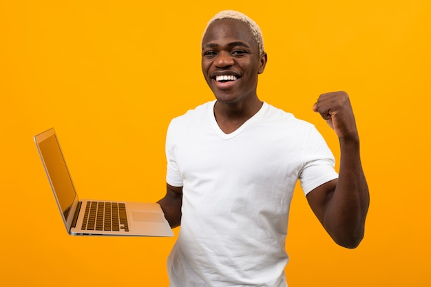 Czarny amerykanin z pięknym śnieżnobiałym uśmiechem w białej koszulce z laptopem i pomarańczą