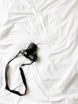 Czarny aparat leżący przy łóżku z białą pościelą. minimalne tło