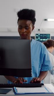 Czarny asystent wpisując leczenie healdcare na komputerze, podczas gdy w tle lekarze chirurgów sprawdzają chorą kobietę pisania diagnozy choroby. pacjent leżący na oddziale szpitalnym podczas konsultacji wraca do zdrowia