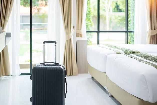 Czarny bagaż w nowoczesnym pokoju hotelowym z oknami, zasłonami i łóżkiem