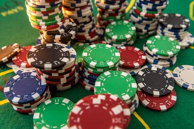 Czarny biały czerwony niebieski zielony stosy żetonów kasyna na zielonym stole do pokera. klub bukmacherski i hazard, zwycięski motyw