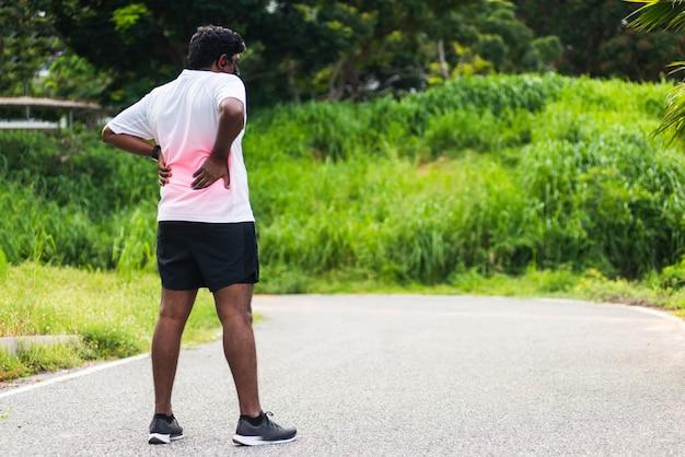 Czarny biegacz nosi zegarek czuje ból na plecach kręgosłupa