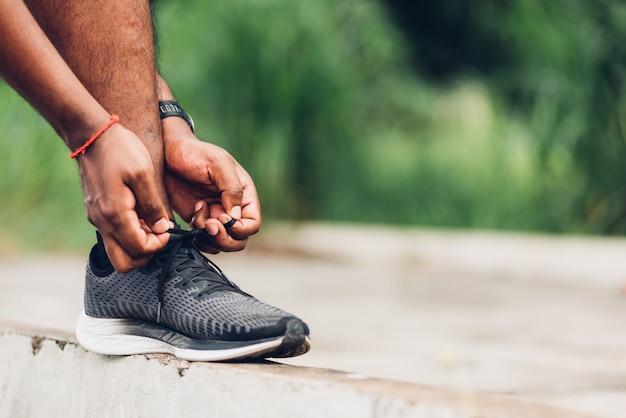 Czarny biegacz nosi zegarek stanąć na chodniku próbując butów do biegania sznurowadło