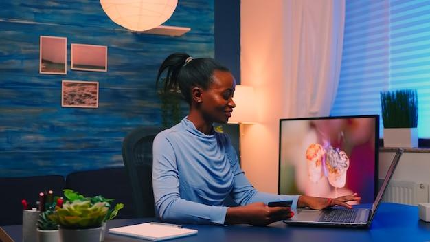Czarny biznes kobieta dokonywania transakcji z domu za pomocą karty kredytowej, siedząc w salonie późno. freelancer robiący zakupy online z domu z płatnością elektroniczną na cyfrowym notebooku podłączonym do internetu