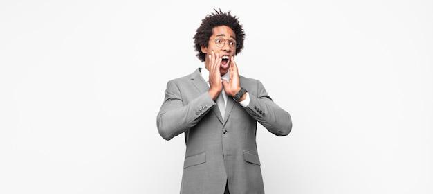 Czarny biznesmen afro czując się szczęśliwy, podekscytowany i zaskoczony, patrząc w bok z obiema rękami na twarzy