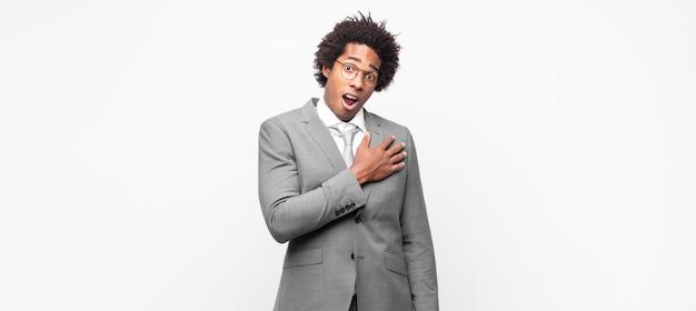 Czarny biznesmen afro czuje się zszokowany i zaskoczony, uśmiecha się, bierze ręce do serca, jest szczęśliwy, że jest tym jedynym lub okazuje wdzięczność