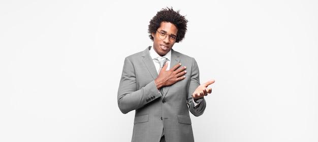 Czarny biznesmen afro, szczęśliwy i zakochany, uśmiechnięty z jedną ręką obok serca, a drugą wyciągniętą z przodu
