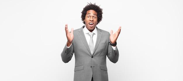 Czarny biznesmen afro wyglądający na zszokowanego i zdziwionego, ze zdziwieniem opadającą szczęką, gdy zdał sobie sprawę z czegoś niewiarygodnego